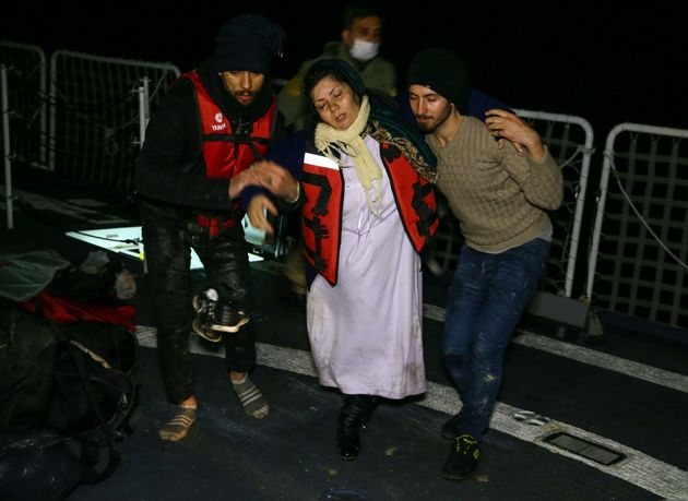 Turkish coast guards pull an Afghan refugee, 8.5 months pregnant, into a Coast Guard ship, during a rescue...