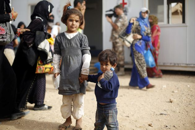 Syrian refugees wait to board a Jordanian army vehicle after crossing into Jordanian territory with their