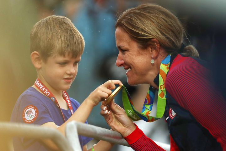 Kristin Armstrong shows her medal to her son, Lucas,after the medal ceremony.