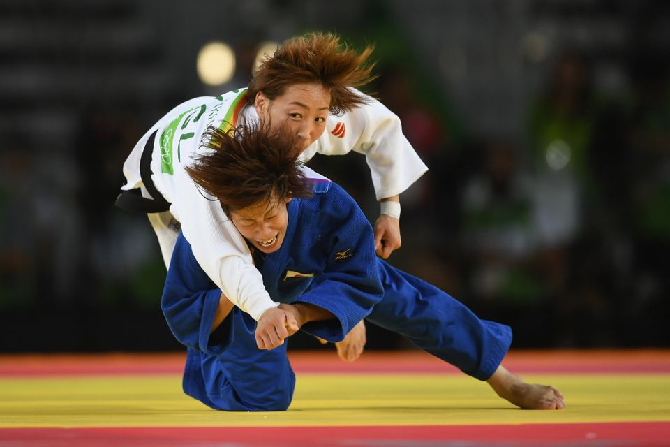 Ami Kondo of Japan (blue) takes down Urantsetseg Munkhbat of Mongolia during the women's 48kg Bronze Medal A judo contest on