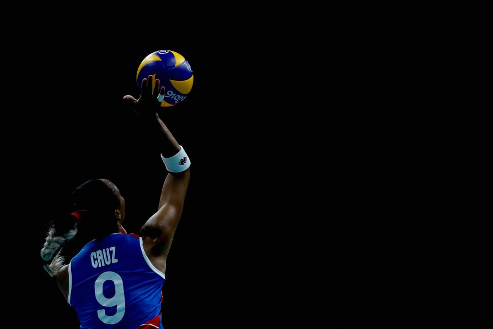 Aurea Cruz of Puerto Rico spikes the ball during the women's qualifying volleyball match between China and Puerto Rio on Day