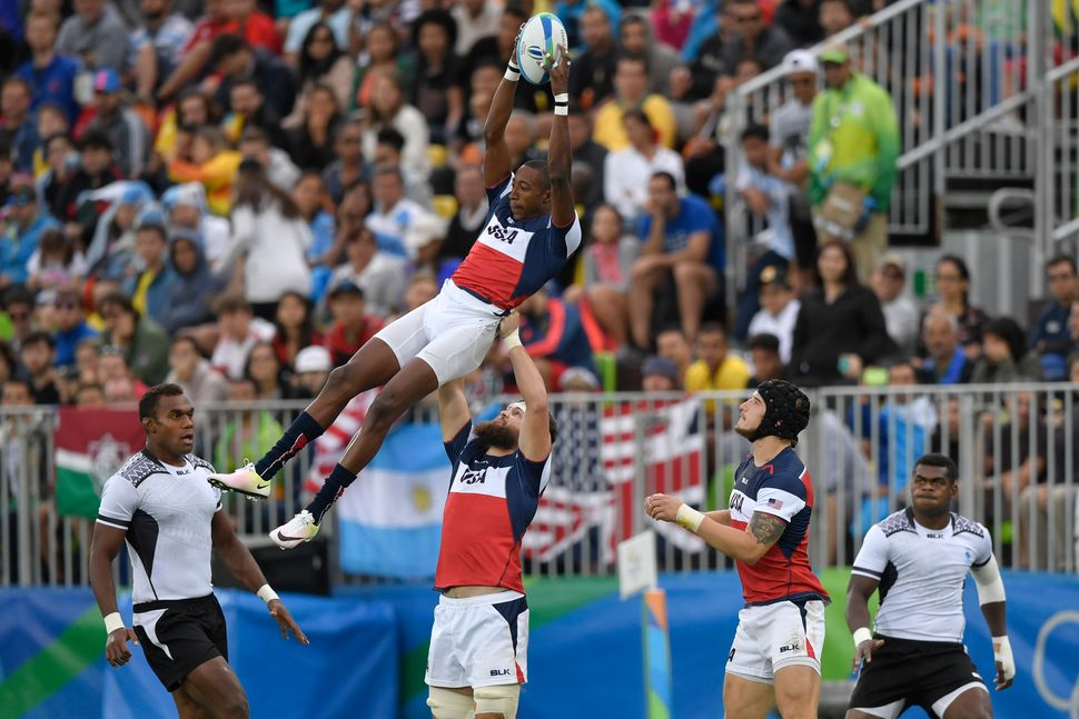 USA's Perry Baker catches the line-out ball in the men's rugby sevens match between Fiji and USA during the Rio 2016 Olympic