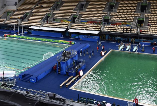 The Olympic water polo pool, at left, began turning green