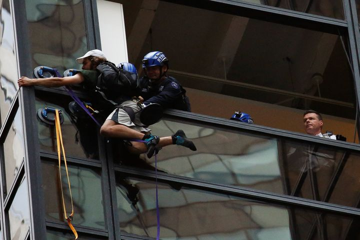 Officers from the NYPD embrace a man to stop him from climbing the outside of Trump Tower in New York, U.S., August 10, 2016.