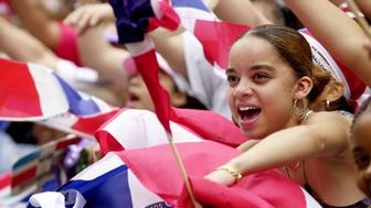UNITED STATES - CIRCA 2000:  Keyla Brito, 15, gives a cheer amid a swirl of flags at the Dominican Day Parade on Sixth Ave.  (Photo by Mitsu Yasukawa/NY Daily News Archive via Getty Images)
