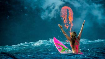 PIC BY PERRIN JAMES / CATERS NEWS - (PICTURED: Alison Teal paddles out to Kilauea volcano in Hawaii as it eruopts into the ocean) - Professional adventurer Alison Teal has become the first woman to paddle out into lava during a volcanic eruption into the sea. Amazing shots of the extreme surf session shows the daredevil riding her pink surfboard up to the base of Kilauea Volcano. Photographer Perrin James snapped the brave explorer within feet of the lava as it flows into the ocean. Its the first the volcano in the Big Island of Hawaii has erupted since 2011. SEE CATERS COPY