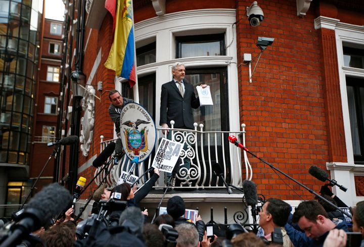 WikiLeaks founder Julian Assange holds a copy of a U.N. ruling as he makes a speech from the balcony of the Ecuadorian Embass