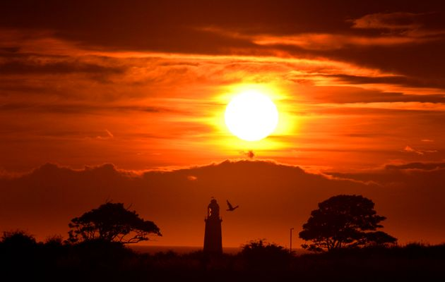 The sun rises over Whitley Bay with the top of St Mary's lighthouse