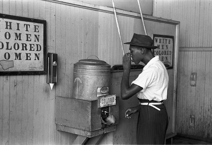 """Colored"" drinking fountain from mid-20th century with african-american drinking (Original caption from July 1939: ""Negro dri"