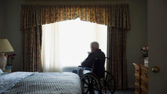 Senior man in wheelchair looking through bedroom window