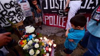 Young boys stand near a memorial for 14-year-old Jesse Romero in the Boyle Heights section of Los Angeles, California August 10, 2016 near the spot where the middle school student was fatally shot by a police officer August 9, 2016.  Romero, who was suspected of writing gang-style graffiti, was shot and killed after he bolted from police and fired a gun at them, according to the Los Angeles Police Department said. / AFP / Robyn Beck        (Photo credit should read ROBYN BECK/AFP/Getty Images)