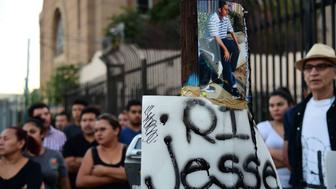 People gather for a vigil for 14-year-old Jesse Romero in the Boyle Heights section of Los Angeles, California August 10, 2016 near the spot where the middle school student was fatally shot by a police officer August 9, 2016.  Romero, who was suspected of writing gang-style graffiti, was shot and killed after he bolted from police and fired a gun at them, according to the Los Angeles Police Department said. / AFP / Robyn Beck        (Photo credit should read ROBYN BECK/AFP/Getty Images)