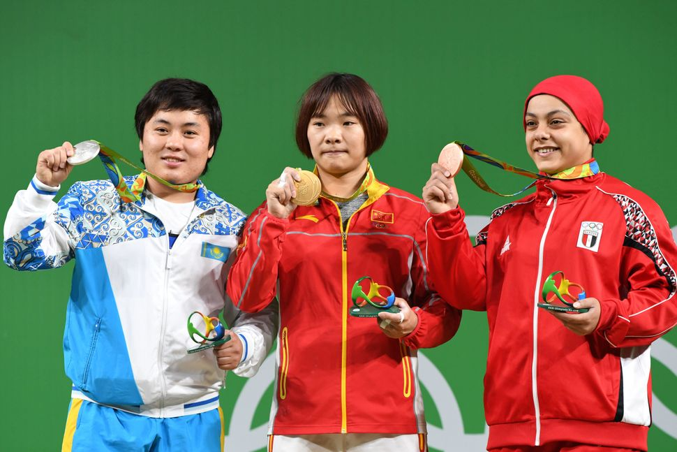 Sara Ahmed, right, stands on the podium with China's Xiang Yanmei, center, and Kazakhstan's Zhazira Zhapparkul, lef