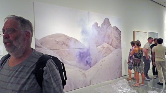Artist Galen Brown stands before work by Timothy Conder, Nick Larsen, and Omar Pierce in Tilting the Basin.