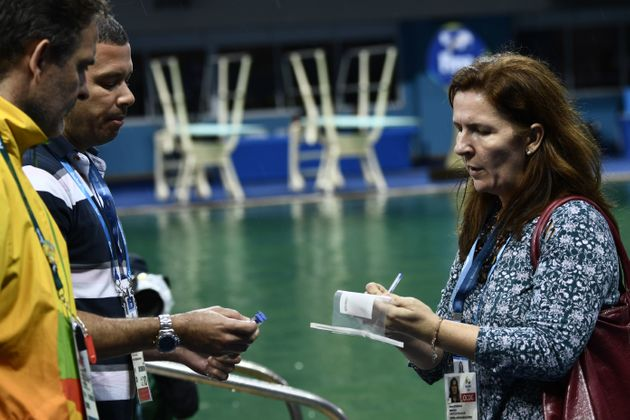 Experts get ready to take samples of the diving pool waterat the Maria Lenk Aquatics Stadium in...