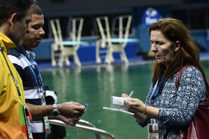 Experts get ready to take samples of the diving pool waterat the Maria Lenk Aquatics Stadium in Rio de Janeiroon