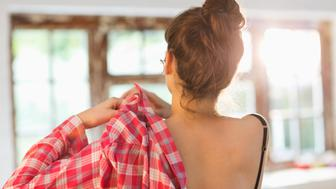 Woman putting on shirt in bedroom