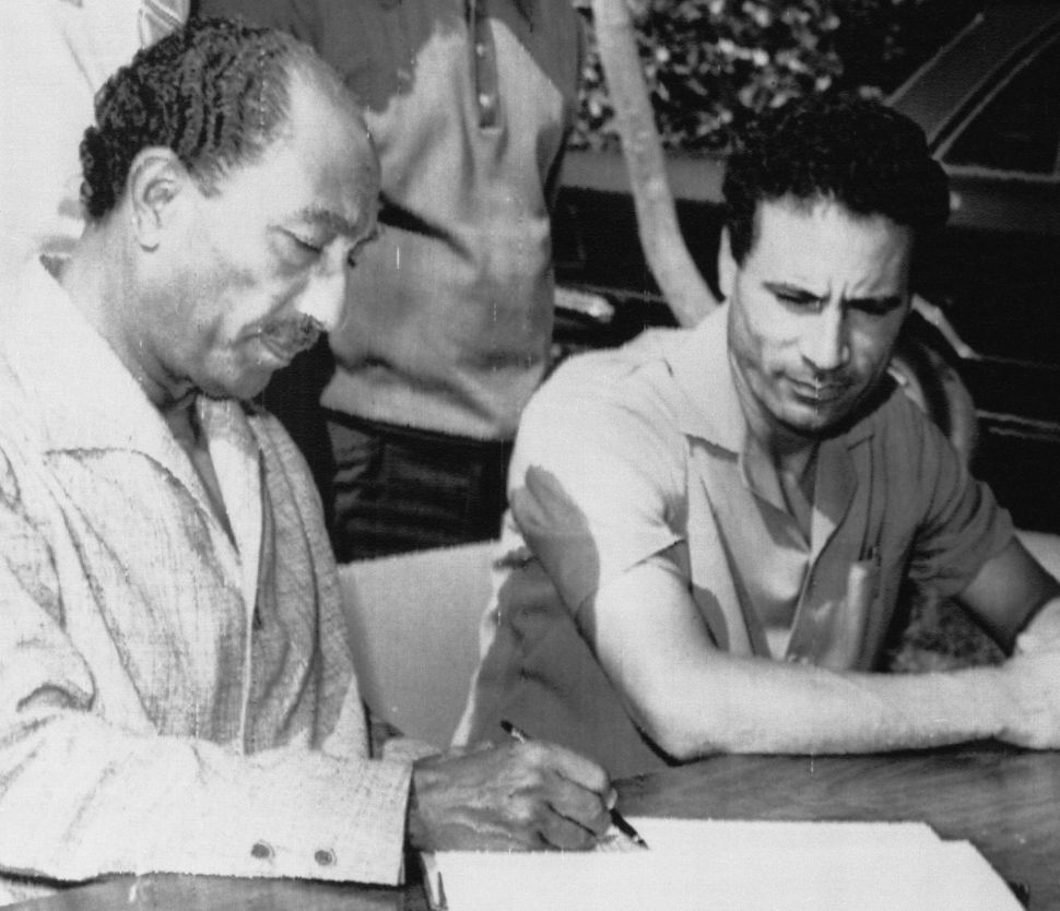 Sadat, left, and Gaddafi look over a communiqué after agreeing to merge their two countries on Sept. 7, 1973.