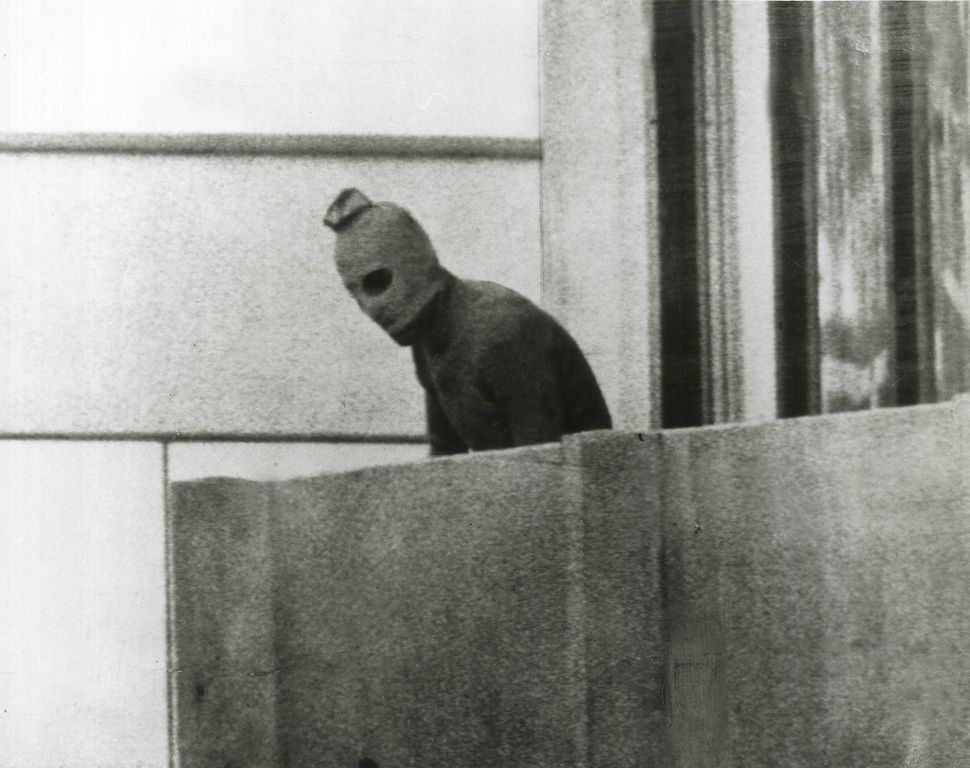 A Palestinian terrorist peers over the balcony of a room in the Olympic Village, where Israeli athletes were being held hosta