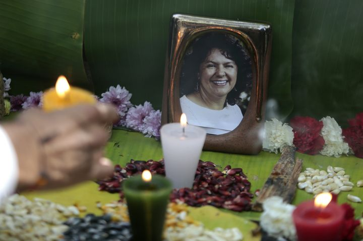 An activist places a candle in an offering to slain Honduran indigenous environmentalist Berta Cáceres. U.S. aid