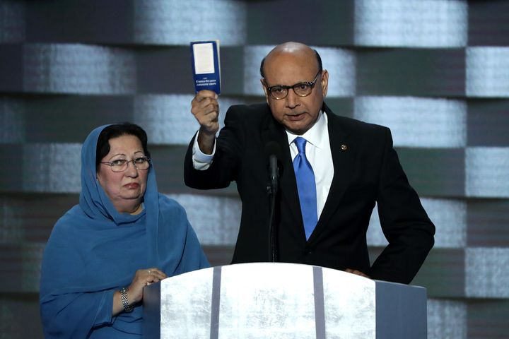 Khizr Khan holding up a copy of the Constitution at the Democratic National Convention on July 28, 2016. Ghazala Khan (L) sto
