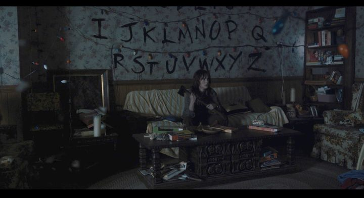 Joyce Byers (Winona Ryder) keeps watchful guard in her home, axe in hand.