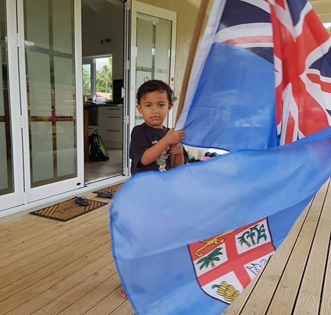 A Samoan child with a Fiji flag in Cook Islands.