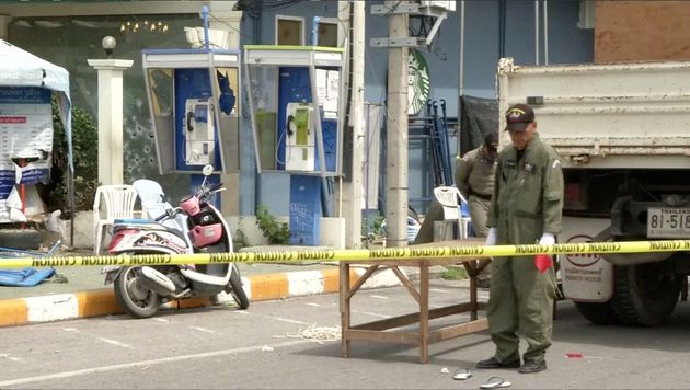 Police Explosive Ordnance Disposal official inspects the site of a bomb blast in Hua