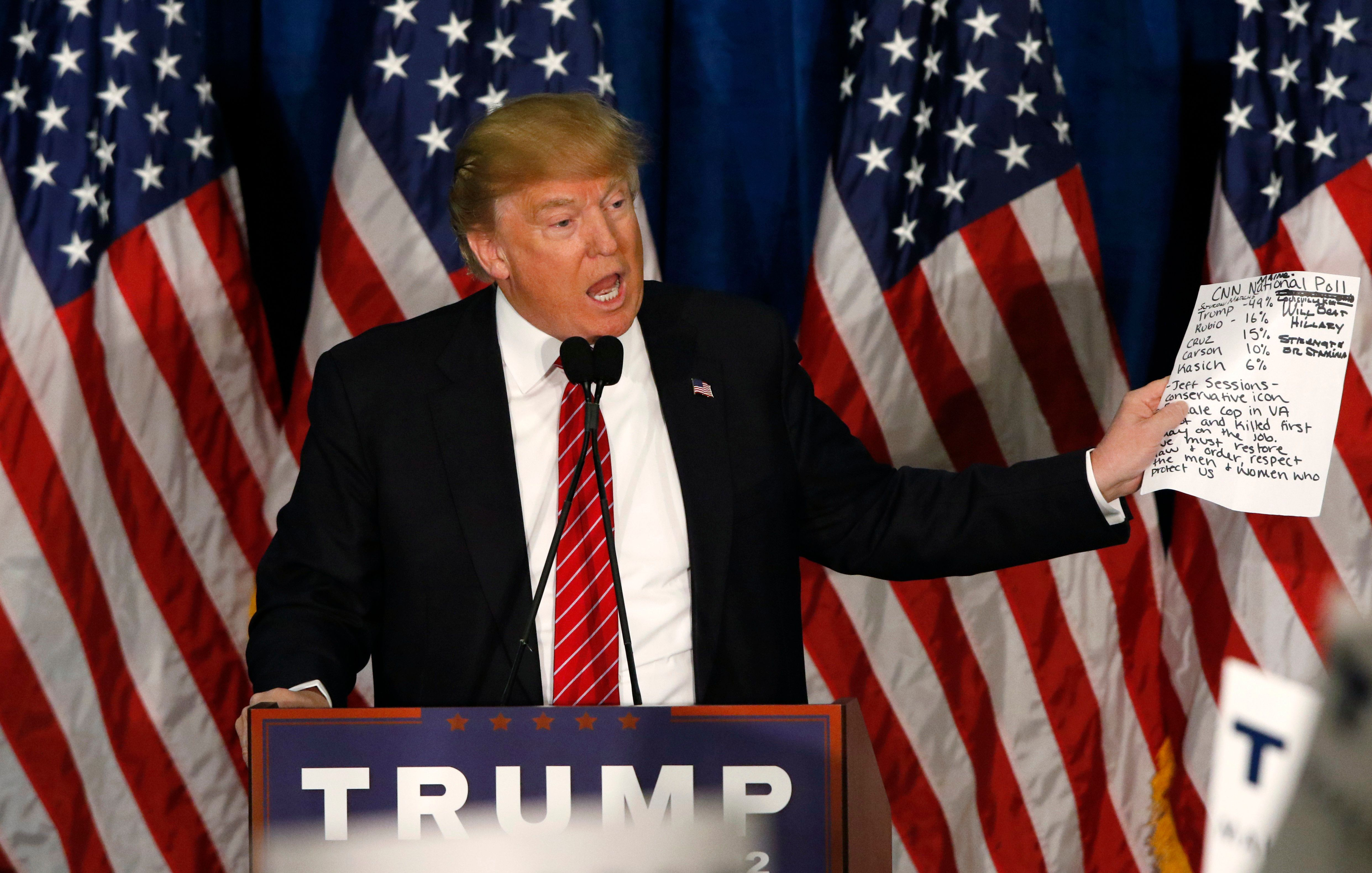 Donald Trump holds up a CNN poll as he talks about his poll numbers at a rally in Portland, Maine.