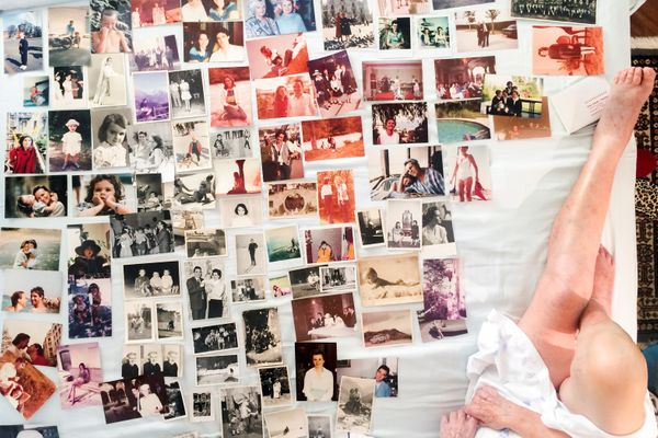 Old family photographs are seen on Marisa Vesco'•s bed as she works on creating a family album with her granddaughter, the ph