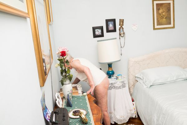 Marisa Vesco reaches for a magazine in a bedroom of her apartment in Cossato, Italy, June 7, 2015.