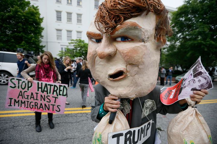 A masked protester demonstrates outside Republican National Committee (RNC) headquarters, where Republican U.S. presidential
