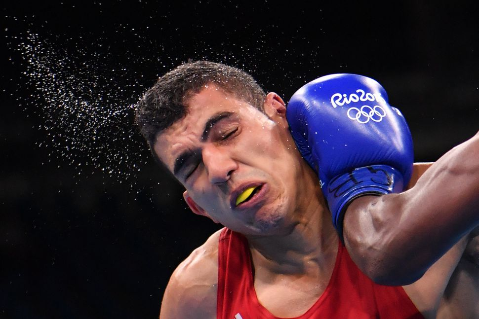 Morocco's Mohammed Rabii is punched by Kenya's Rayton Nduku Okwiri during the Men's Welter (69kg) match.