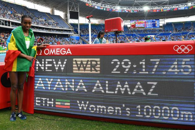 Ethiopia's Almaz Ayana celebrates next to a board displaying her new world record for the women's 10,000...