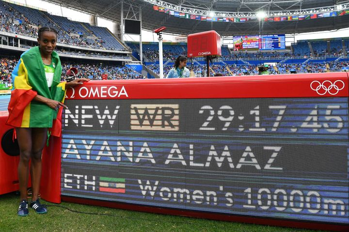 Ethiopia's Almaz Ayana celebrates next to a board displaying her new world record for the women's 10,000 meters at the Rio Ol