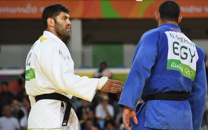 Israel's Or Sasson, left, attempts to shake the hand of Egypt's Islam El Shehaby after their men's +100kg judo matc