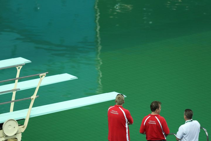 Officials look at the Olympic diving pool on Tuesday. It's definitely green.