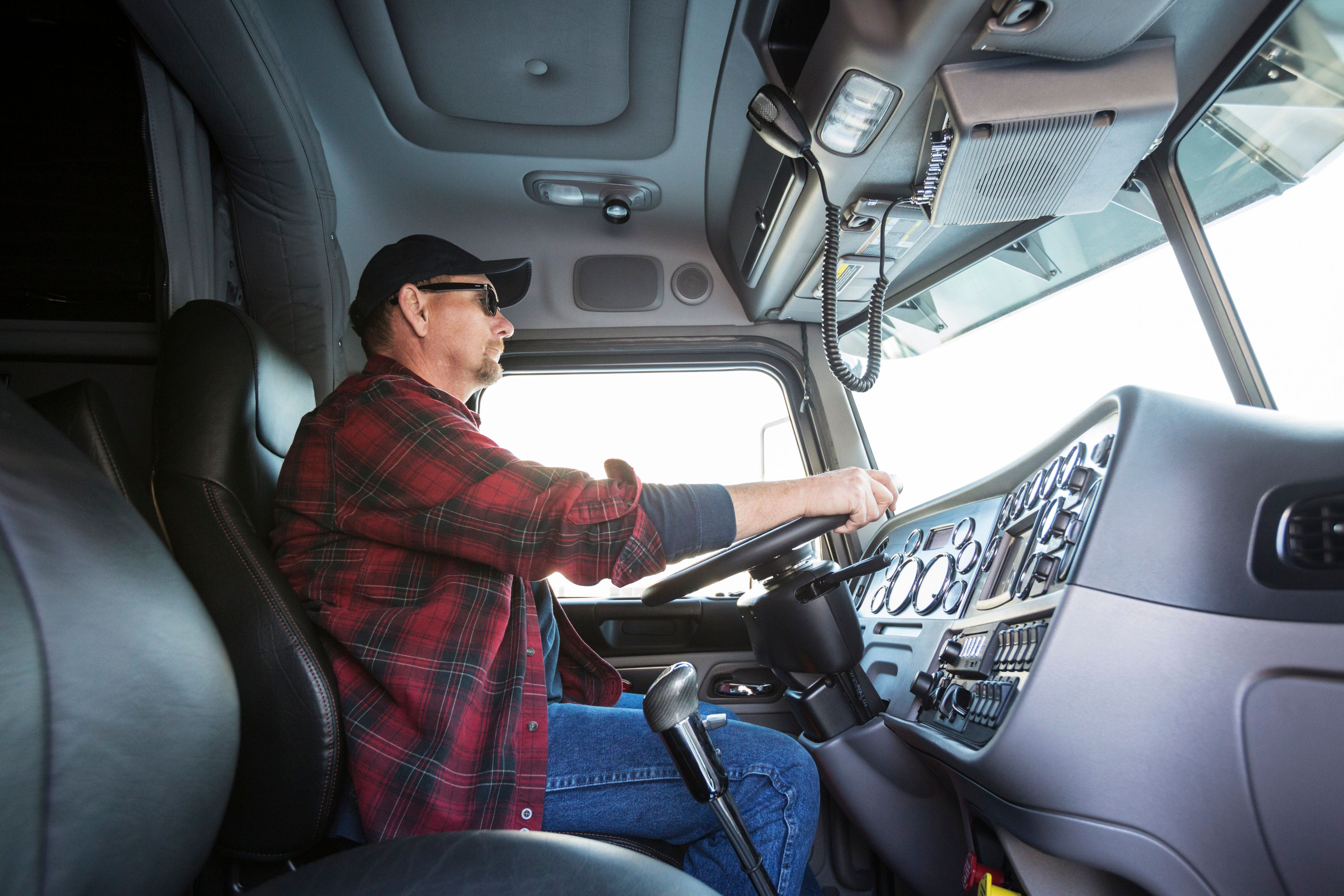 Truck driver at wheel in cab of truck