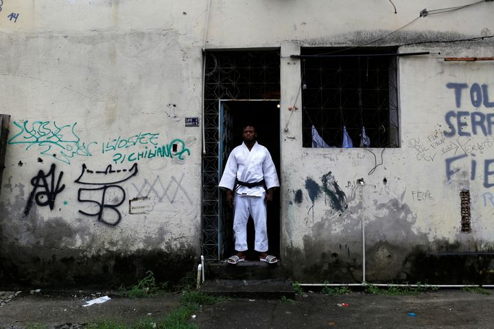 Popole Misenga, a refugee from the Democratic Republic of Congo and a judo athlete, poses at the entrance of his home in a sl