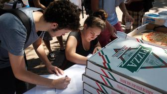 College of Charleston students Trevor Catalano (left) and Ashley Gennarelli, both of Greenville, South Carolina, fill out a voter registration form while waiting in line for a slice of pizza at a Rock The Vote student registration drive on campus in Charleston, South Carolina, Thursday, September 27, 2012. Both students are first time voters, registering at the event sponsored by the student government association and The Bully Pulpit. Students were treated to soft drinks and t-shirts in addition to pizza. (Randall Hill/MCT via Getty Images)