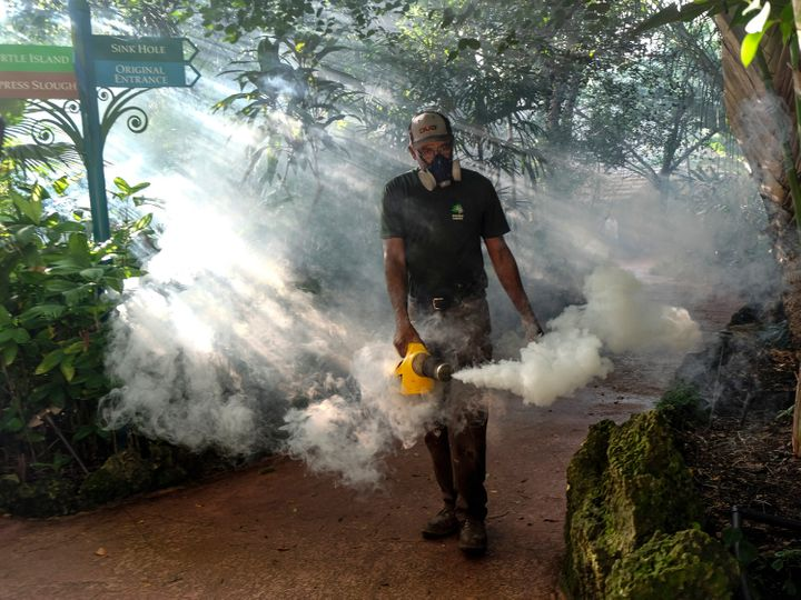 Fran Middlebrooks uses a blower to spray pesticide to kill mosquitos Aug. 4, 2016 in Miami, as Miami Dade county fights to control the Zika virus outbreak.