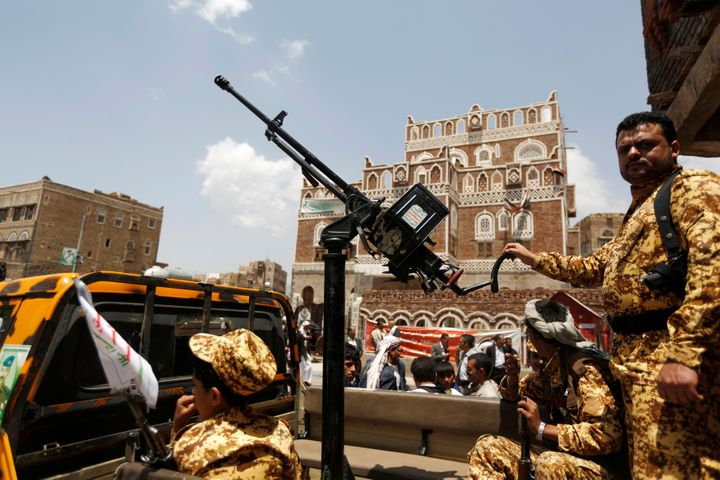 A soldier holds a machine gun mounted on a police truck outside Yemen's parliament during the first parliament sessions