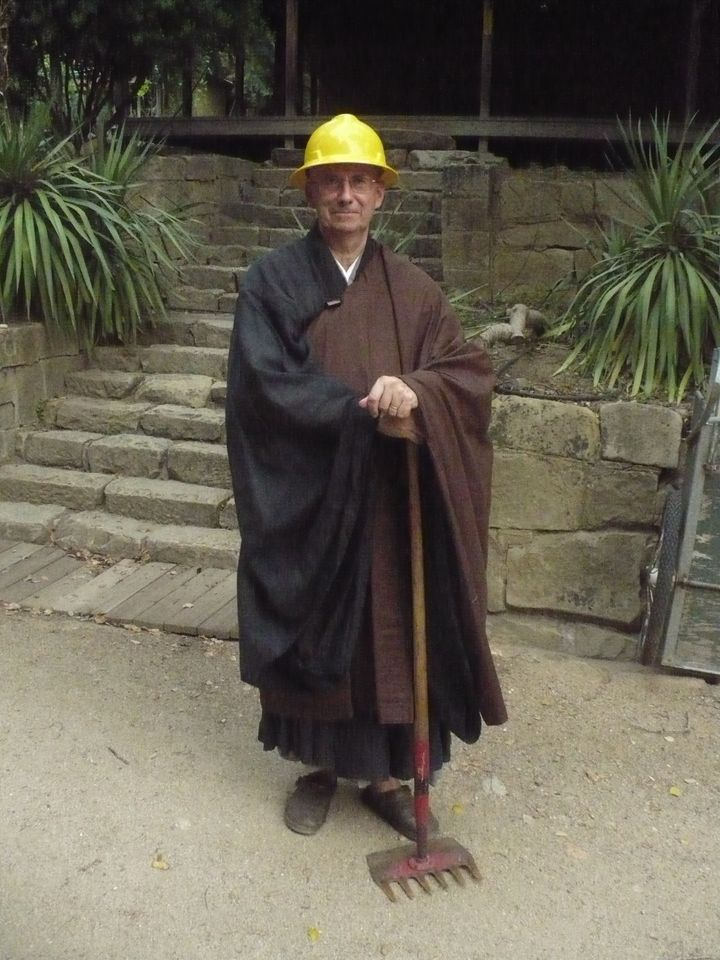Abbot Steve posing in his robes with fire gear after the 2008 Basin Complex fire.