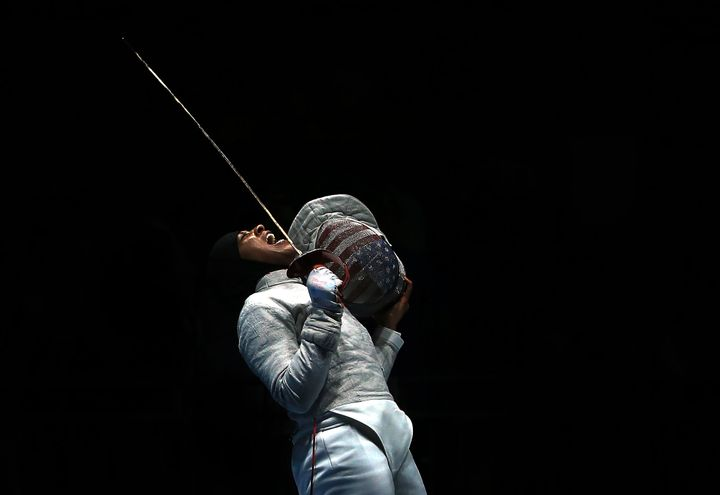 Ibtihaj Muhammad celebrates a point over Ekaterina Dyachenko of Russia in the Women's Sabre Team Semifinals of the Rio Olympi