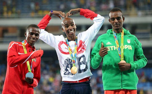 Paul Kipngetich Tanui (KEN) of Kenya, Mo Farah (GBR) of Britain and Tamirat Tola (ETH) of Ethiopia pose...