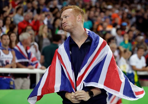 Britain's Greg Rutherford celebrates with the British flag after winning the bronze medal in the men's...