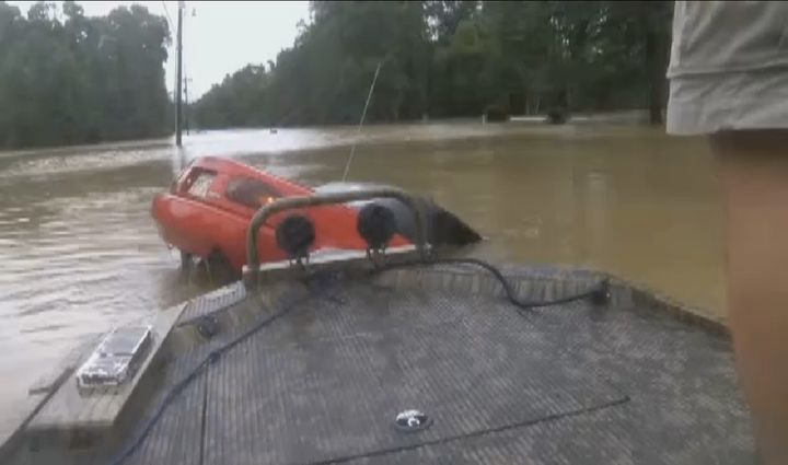 Several boaters are seen coming upon a sinking car following historic flooding across Louisiana.
