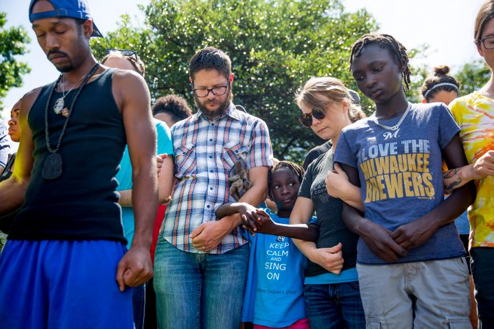 People link arms during a group prayer across the street from a gas station on Aug. 14, 2016 in Milwaukee, Wisconsin. The gas