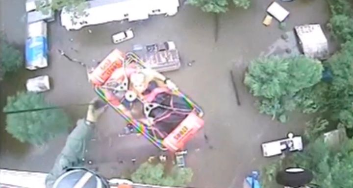 An aircrew from Coast Guard Air Station New Orleans rescues three people from a rooftop in Baton Rouge.