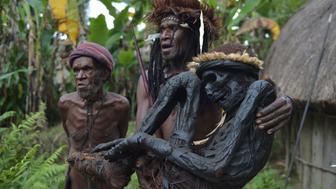 TOPSHOT - This photo taken on August 7, 2016 shows tribe chief Eli Mabel (C) holding the mummified remains of his ancestor, Agat Mamete Mabel, Agat Mamete Mabel, in the village of Wogi in Wamena, the long-isolated home of the Dani tribe high in the Papuan central highlands. Despite smoked mummification being no longer practised for Dani tribes people, they still preserve a number of mummies, some a few hundred years old, as a symbol of their highest respects to their ancestors, which in recent years has attracted tourists from around the world. / AFP / ADEK BERRY        (Photo credit should read ADEK BERRY/AFP/Getty Images)